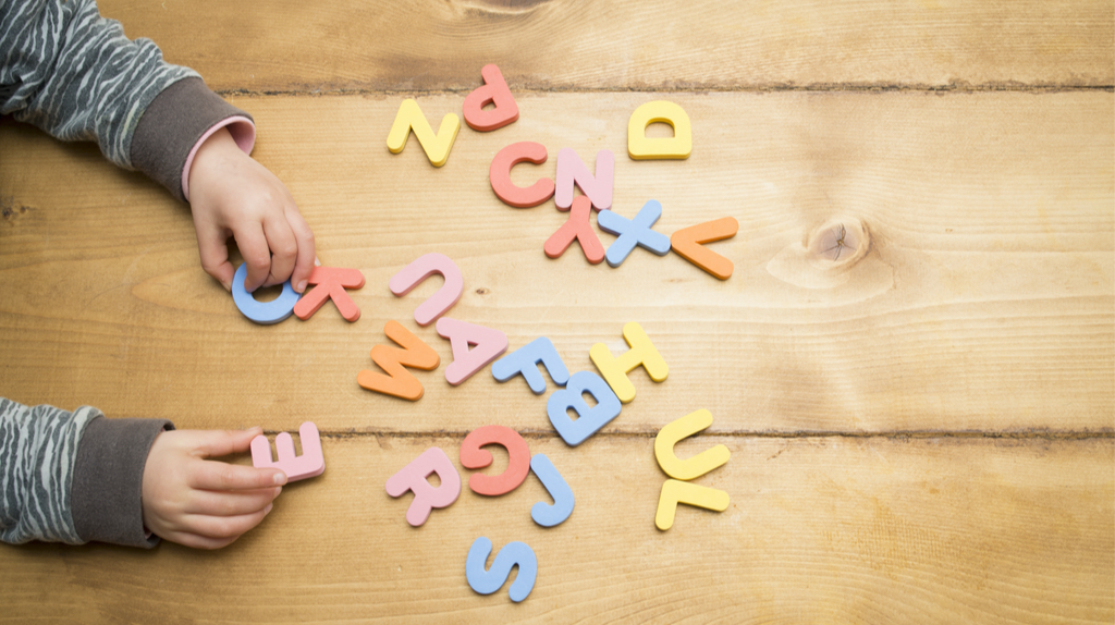 Child playing with scattered alphabets