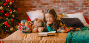 Little girl reading a book during Christmas.